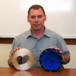 Steve Geary,Senior Machinist Machine Shop at CDH Proton Center, a ProCure Center , holds a brass aperture (left) and a range compensator (right). Each Proton Therapy patient receives a unique set for treatment.